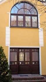 Rundbogenfenster und Eingangsportal aus Holz